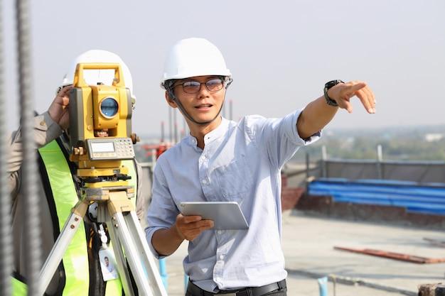 Los ingenieros y el personal están inspeccionando los edificios con teodolito.