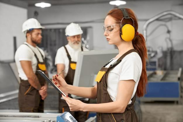 Ingenieros que trabajan con cortador láser de plasma en fábrica.