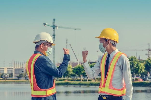 Los ingenieros se saludan tocando los codos, dos hombres de negocios se dan la mano sin tocar la construcción al aire libre en el sitio