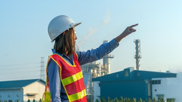 Los ingenieros de seguridad profesionales usan chaquetas de seguridad y señalan a la fábrica.