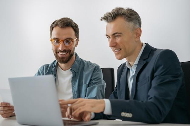 Ingenieros de software exitosos usando laptop, hablando, cooperando trabajando juntos en la oficina