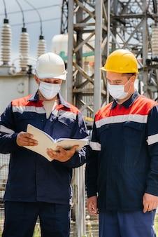 Los ingenieros subestaciones eléctricas realizan una encuesta de equipos modernos de alto voltaje en la máscara en el momento de la pandemia. energía. industria.