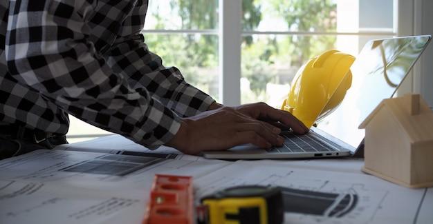 Los ingenieros usan computadoras portátiles y revisan el plano