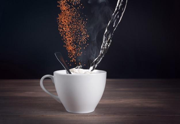 Ingrediente para café en una taza blanca y café molido en grano en el aire sobre un fondo oscuro.