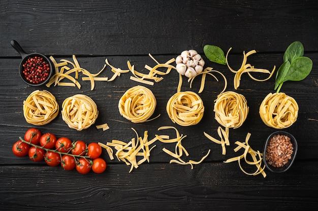 Ingrediente de la cocina tradicional mediterránea, tagliatelle de pasta cruda, sobre mesa de madera negra, vista superior laicos plana