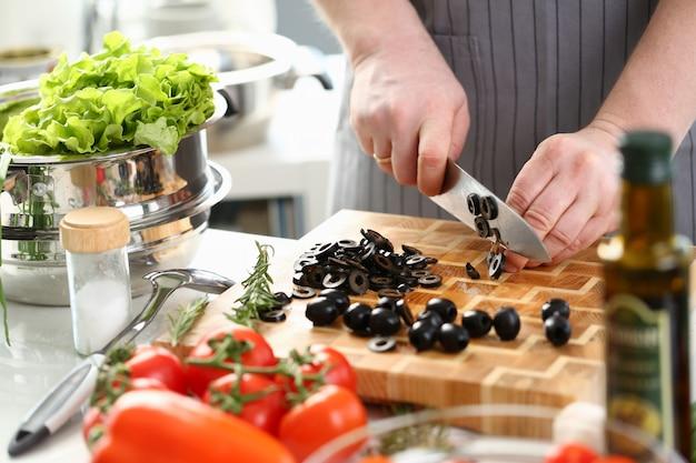 Ingrediente de ensalada de oliva rebanado de chef profesional