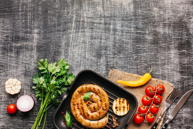 Ingrediente fresco y sabroso y salchichas fritas de caracol en el fondo de la textura de madera gris