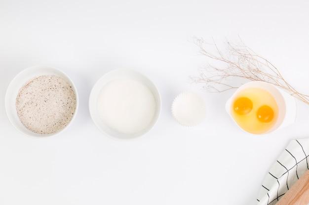 Ingrediente para hornear crudo dispuesto en fila sobre superficie blanca