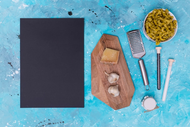 Ingrediente de pasta cruda; pizarra; tabla de cortar y rallador sobre fondo manchado