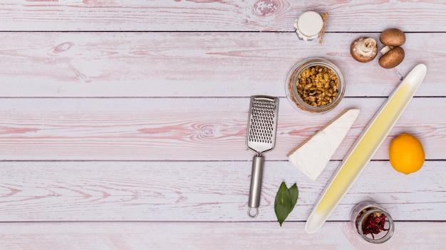 Ingrediente saludable con rallador inoxidable sobre mesa de madera