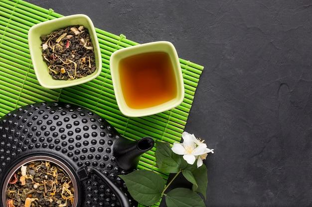 Ingrediente de té de hierbas seco aromático en lugar estera sobre fondo de piedra negro