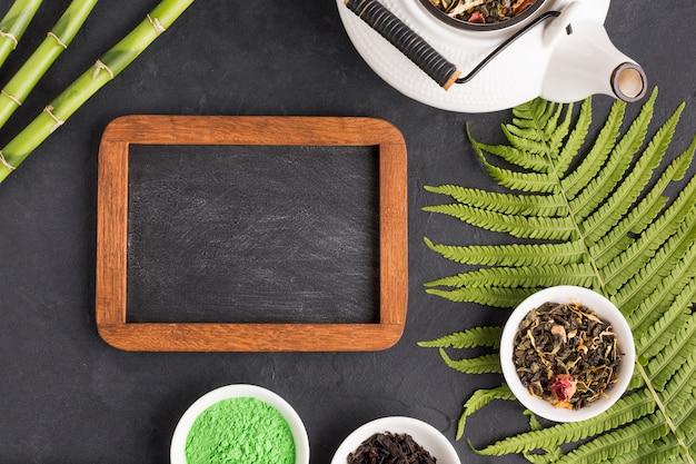 Ingrediente de té saludable con pizarra vacía y tetera sobre fondo negro