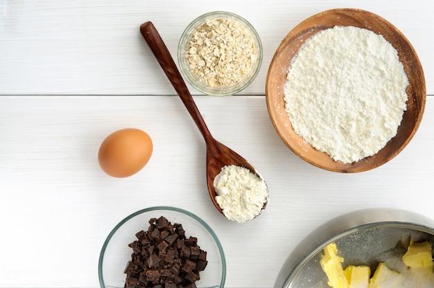 Ingredientes alimentarios y utensilios de cocina para cocinar galletas de avena sobre fondo blanco de madera. vista plana superior