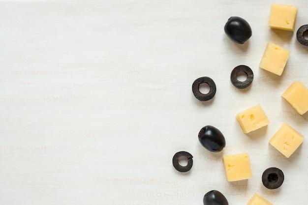 Ingredientes para aperitivos, queso con aceitunas sobre una mesa blanca.