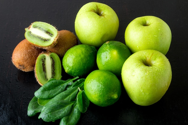Ingredientes para batido, frutas verdes sobre superficie de madera negra