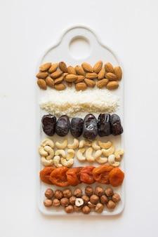 Ingredientes y bolas de fechas de energía con cacao y nueces en blanco. comida saludable para veganos y niños.