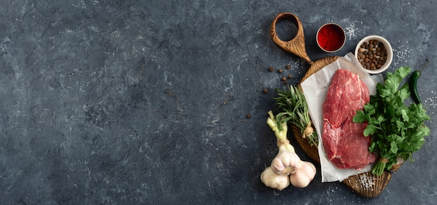 Ingredientes de carne cruda en tablero de madera coutting en piedra oscura con vista superior de copyspace. menú del restaurante