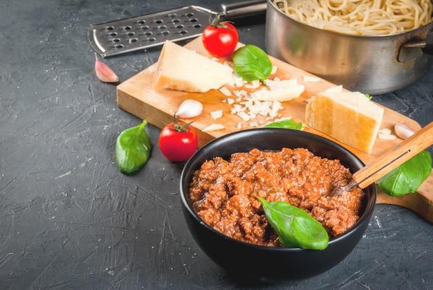Ingredientes de la cocina italiana. productos para la preparación de pasta boloñesa, el proceso de cocción. espagueti soldado en sartén, salsa boloñesa, albahaca, ajo, tomate, parmesano