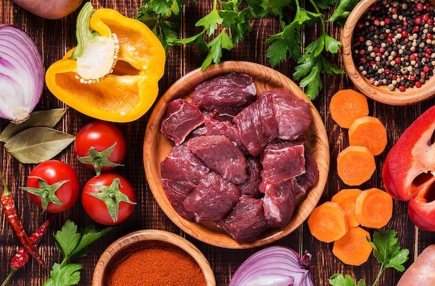 Ingredientes para cocinar estofado o estofado: carne cruda, hierbas, especias, verduras en la superficie de madera oscura