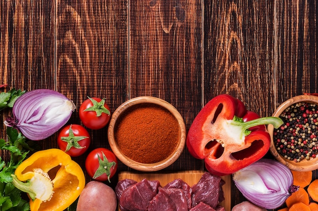 Ingredientes para cocinar goulash o estofado: carne cruda, hierbas, especias, verduras en madera oscura.