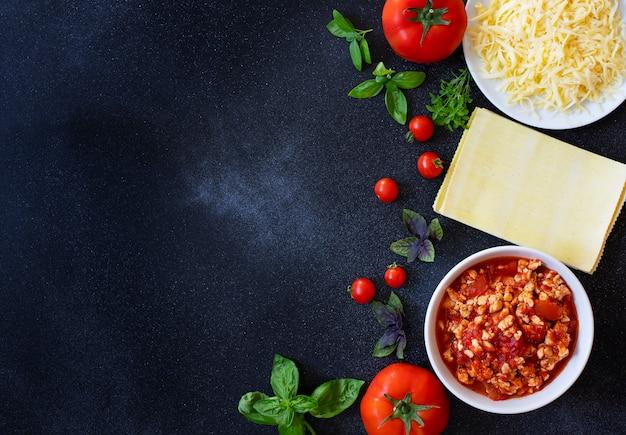 Ingredientes para cocinar lasaña. receta de lasaña italiana casera con salsa de tomate y carne. tomates, albahaca, salsa de carne, queso mozzarella, fideos de lasaña. comida italiana. vista superior. copia espacio