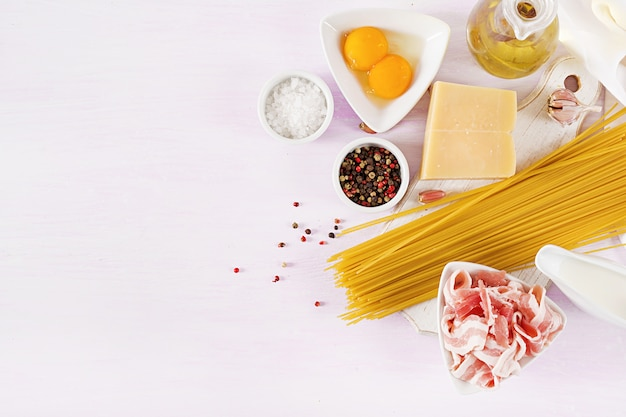 Ingredientes para cocinar pasta carbonara, espaguetis con panceta, huevo, pimientos, sal y queso parmesano duro.