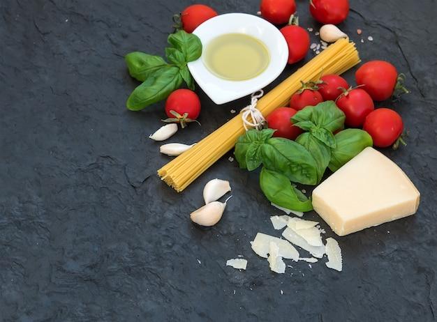 Ingredientes para cocinar pasta. espagueti, aceite de oliva, ajo, queso parmesano, tomate y albahaca fresca.