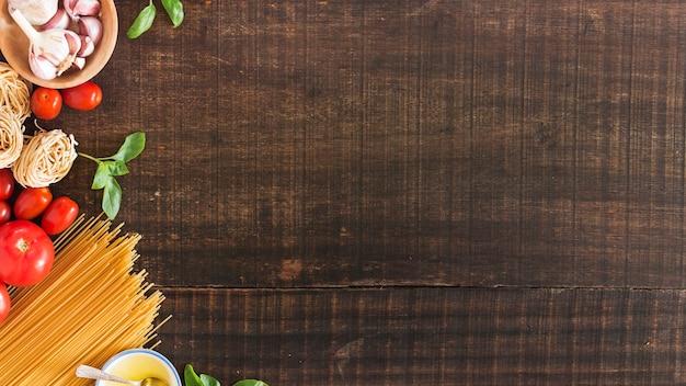 Ingredientes para cocinar pasta sobre fondo de madera.