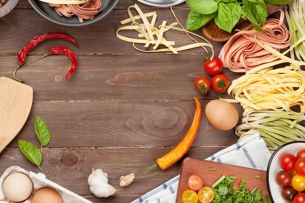 Ingredientes para cocinar pasta y utensilios de mesa de madera. vista superior con espacio de copia.