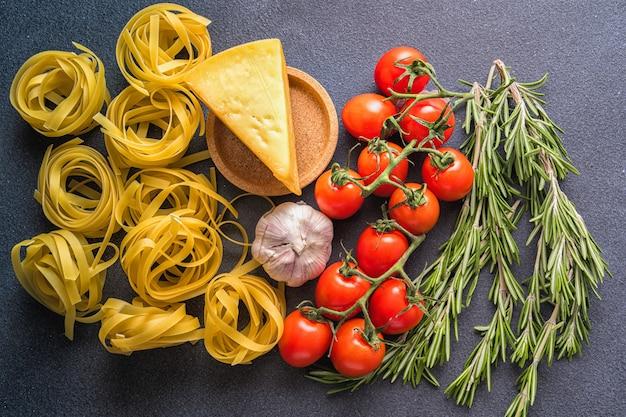 Ingredientes para cocinar pasta, vista superior, endecha plana. pasta, tomate, ajo, romero, pimiento.