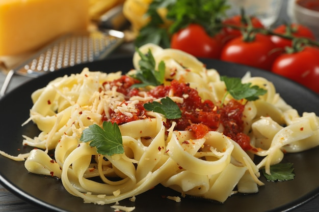 Ingredientes para cocinar y plato de pasta sabrosa, de cerca