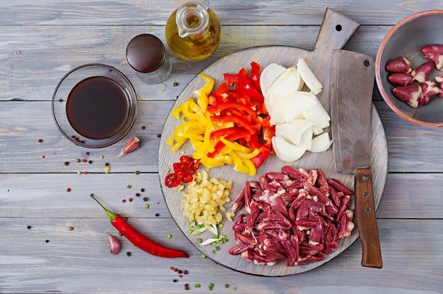 Ingredientes para cocinar salteados de corazones de pollo, pimentón y cebolla. cocina china. vista superior