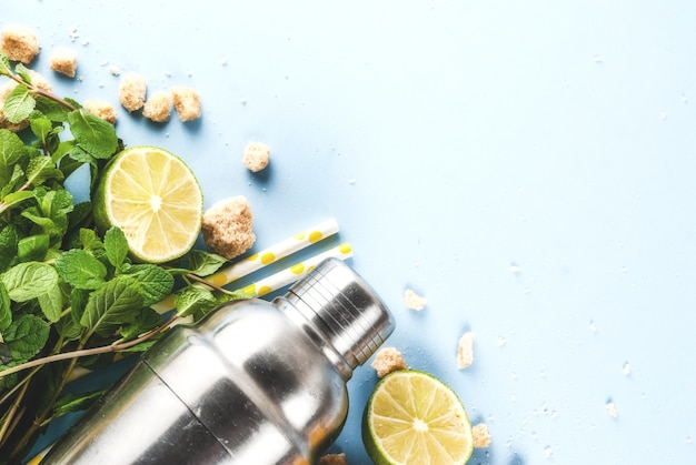 Ingredientes para cóctel mojito o limonada: limón, lima, menta, azúcar, con agitador y pajitas de cóctel. en una superficie azul claro copia espacio vista superior