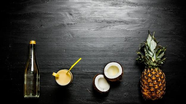 Los ingredientes del cóctel: piña, coco y una botella de ron. espacio libre para texto.