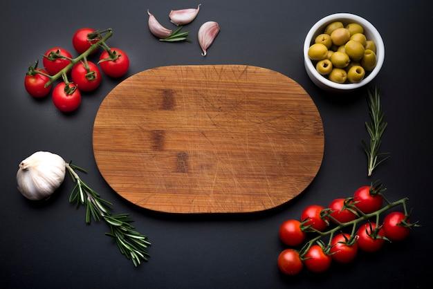 Ingredientes de comida italiana alrededor de tabla de cortar de madera vacía