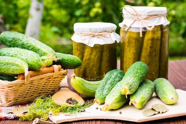 Ingredientes para conservar en vinagre los pepinos en una mesa de madera en el fondo del jardín. pepinos, eneldo, pimiento y laurel. frascos de vidrio con pepinillos