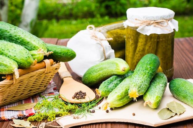 Ingredientes para conservar en vinagre los pepinos en una tabla de cortar el fondo del jardín. pepinos, eneldo, pimiento y laurel. frascos de vidrio con pepinillos