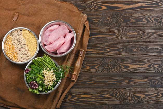 Ingredientes crudos naturales para ingredientes saludables de alimentos para mascotas en cuencos individuales