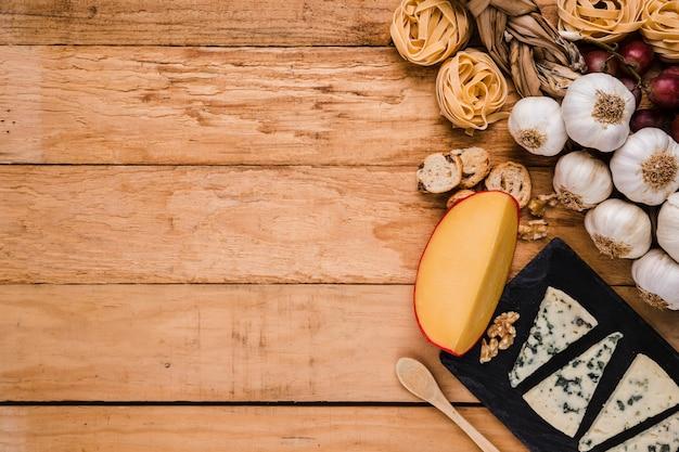 Ingredientes crudos saludables con queso fresco sobre panel de madera con espacio para texto