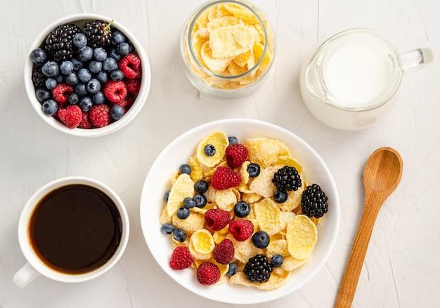Ingredientes para un desayuno saludable: copos de maíz, bayas, leche y café.
