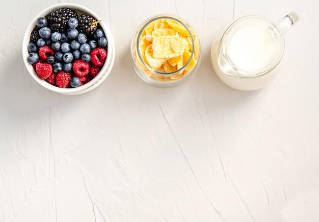 Ingredientes para un desayuno saludable copos de maíz, frambuesas, moras, arándanos sobre una superficie blanca