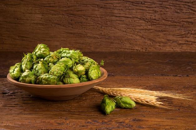 Ingredientes para la elaboración de cerveza conos de lúpulo en un tazón de madera y espigas sobre fondo de madera. concepto de cervecería de cerveza.