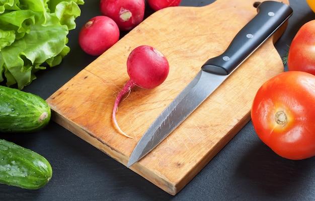 Ingredientes para la ensalada en rodajas sobre tabla de cortar con cuchillo. verduras frescas sobre fondo de pizarra negra. vista superior.