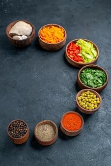 Ingredientes de la ensalada de vista frontal con verduras en la comida madura de ensalada de mesa oscura