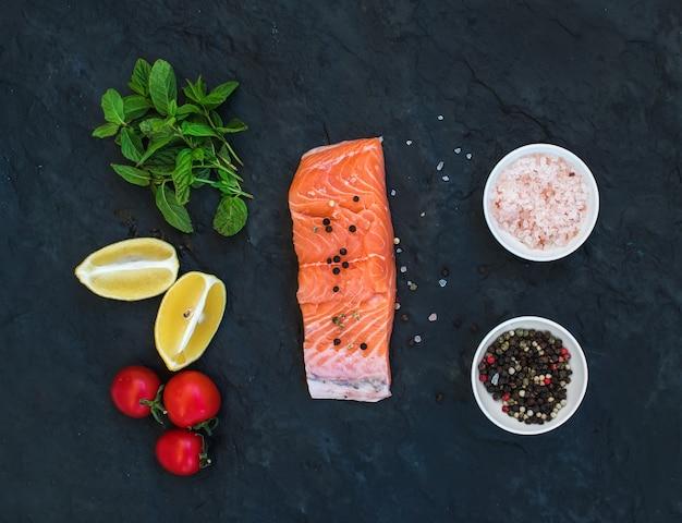 Ingredientes filete de salmón crudo, limón, tomates cherry, menta fresca y especias sobre fondo de piedra oscura
