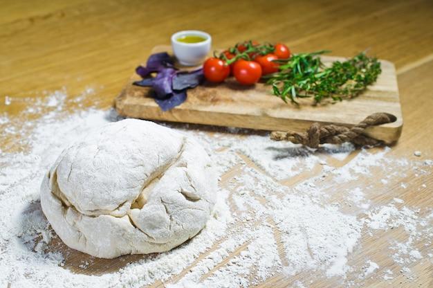 Ingredientes para focaccia: masa, tomates, romero, tomillo, albahaca, aceite de oliva en una mesa de madera.