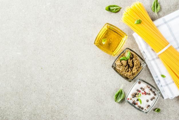 Ingredientes de fondo de alimentos para cocinar la cena. pasta espagueti verduras salsas y especias fondo de piedra gris