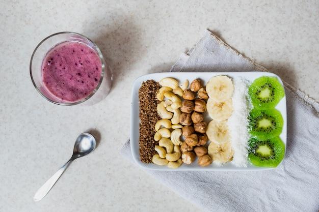 Ingredientes frescos para un desayuno saludable de alimentos crudos. kiwi, hojuelas de coco, anacardos y avellanas disparados desde arriba, ingredientes para un tazón de batido