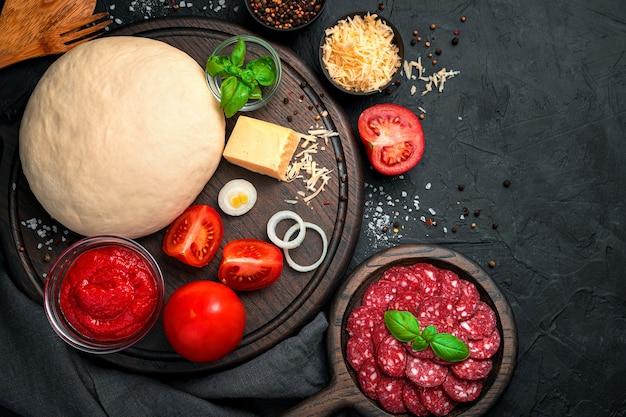 Ingredientes frescos para hacer pizza de pepperoni sobre un fondo de hormigón negro.