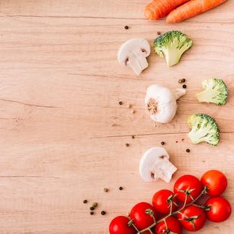 Ingredientes frescos pimienta negra; seta; tomates cherry; bulbo de ajo y zanahoria en superficie de madera